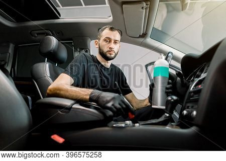 Young Concentrated Male Car Service Worker Cleaning Dust From Interior Of Luxury Car, Using Special