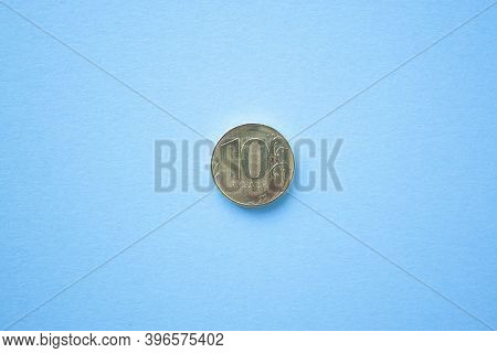 Coin Ten Rouble On Bright Blue Background. Ruble Depreciation. Rouble To Dollar