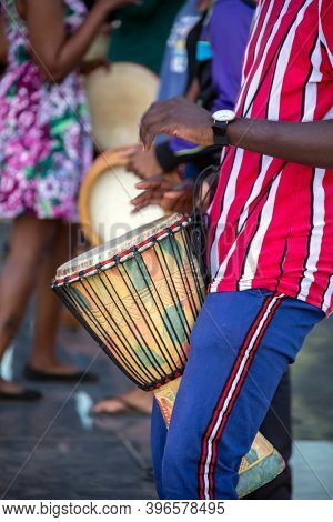 African man playing a traditional drum in a crowd at a festival