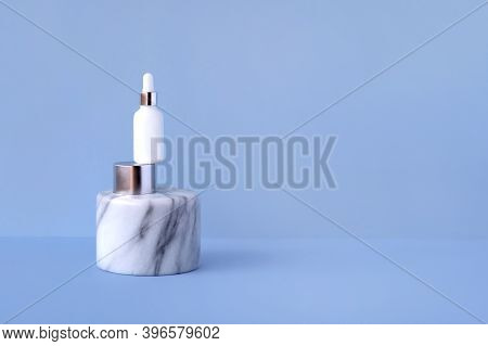 Organic Natural Cosmetic Serum In A White Glass Bottle With A Dropper Pipette On A Marble Aluminum P