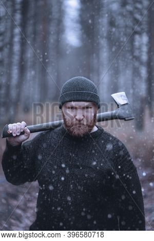Portrait Of A Brutal, Angry And Unfriendly Man With A Beard On His Face And An Axe On His Shoulder.