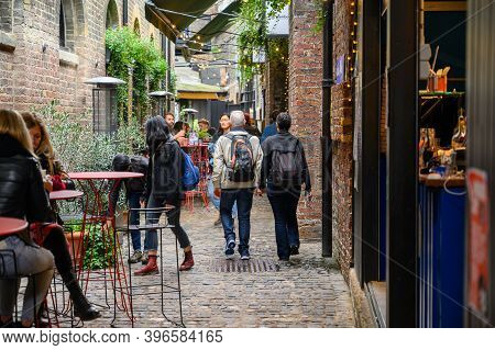 London - September 30, 2019: People Walking Along A Narrow Cobbled Street Passing Food Stalls And Ou