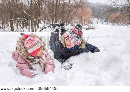 Happy 5-year And 10-year Old Children Playing In The Snow In A City Park In The Open Air.