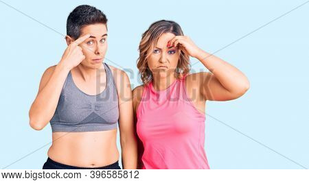 Couple of women wearing sportswear pointing unhappy to pimple on forehead, ugly infection of blackhead. acne and skin problem