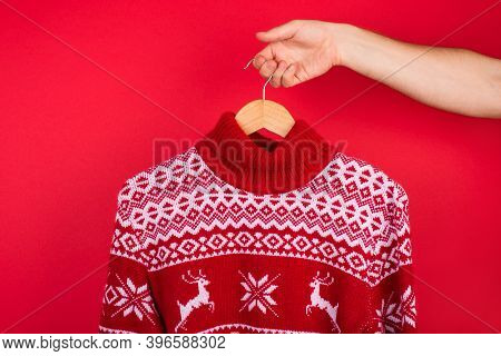 Ugly Christmas Sweater Party Concept. Close Up Photo Of Men Holding Hanger With Red Winter Sweater W