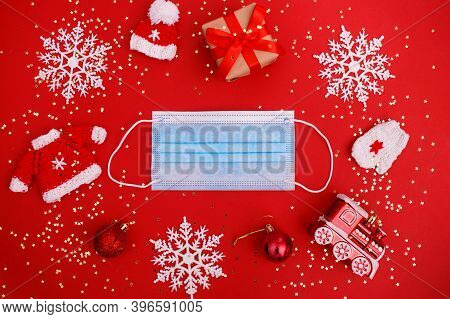 Medical Mask, Christmas Decorations On Red Background With Stars Confetti. Medical Protection Covid-