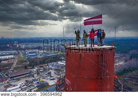 Riga, Latvia. November 18. 2020. People Holding Latvian Flag On Top Of The Tower High Over The Cloud
