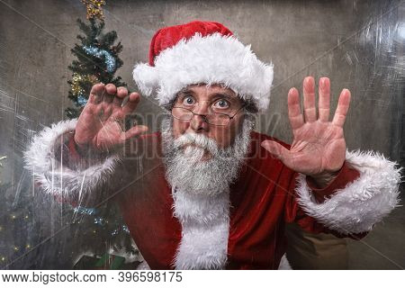 Santa Claus trapped behind scratched acrylic, glass fogging up from Santa's breath