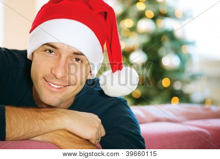 Handsome Young Man wearing Santa's Hat. Christmas Guy Portrait