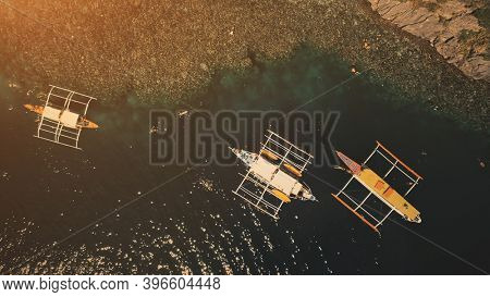 Sunset top down at ocean bay: passengers swim and dive at boats in aerial shot. Tourists leisure at summer cruise tour on traditional vessels. Philippines vacation at tropical island of Palawan