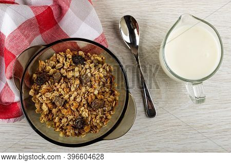 Baked Muesli In Transparent Brown Bowl, Checkered Napkin, Teaspoon, Pitcher With Yogurt On Wooden Ta