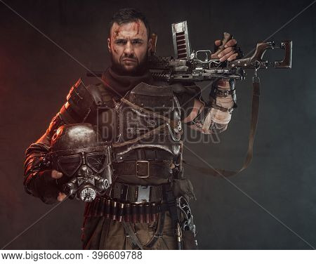 Holding Helmet With Shotgun Survivor Poses In Dark Background Looking At Camera With Serious Face In