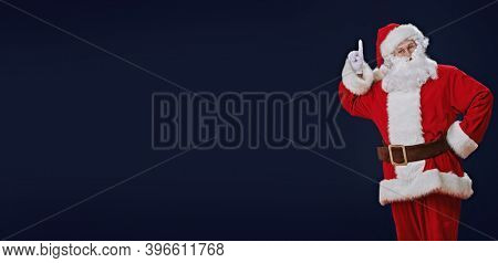 Attention, Christmas! Santa Claus raises his index finger to attract attention. Studio portrait over dark blue background. Copy space.
