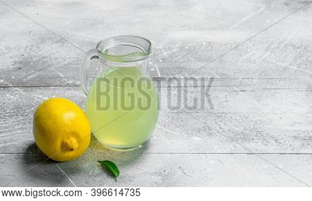 Lemon Juice In The Pitcher. On Rustic Background