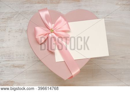 Valentine's Day Holiday.pink Heart Box With Bow ,with White Card On A Light Shabby Chic Background.