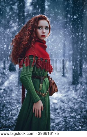 A beautiful red-haired girl of the Middle Ages walks through the winter forest. Christmas tales. Celtic culture. Fantasy world.
