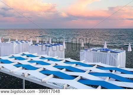 Beach Canopies With Sun Loungers And Umbrellas By The Sea.