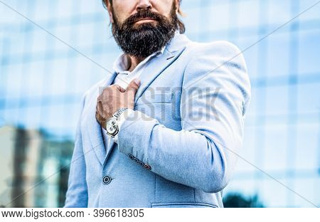Man Holds His Watch. Portrait Successful Businessman In A Business Suit, Using The Watch On A City B