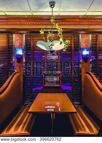 11/26/2020: A Restaurant Table Set With A Retro Looking Lanp Hanging Over And A Classic 1960s Jukebo
