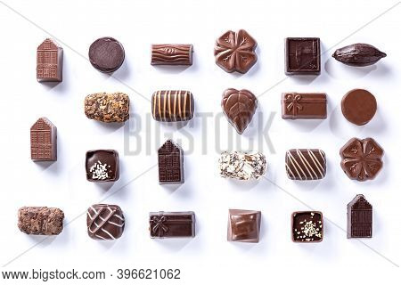Variety Of Chocolate Pralines, Symmetrical Isolated On White Background.  Sweet And Chocolate Concep