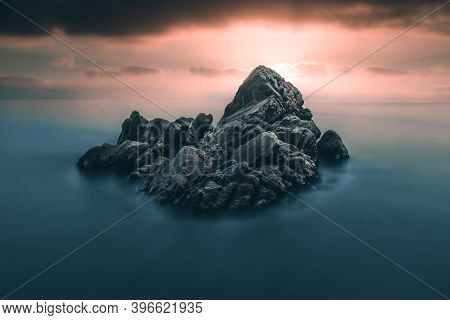 Beautiful Long Exposure With Lonely Rock In Sea Against Sunset/sunrise Dramatic Sky On The Beach Of