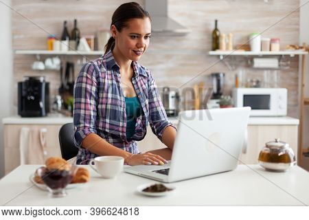 Woman Smiling Using Laptop In Kitchen In The Morning With A Cup Of Hot Green Tea Next To Her. Workin