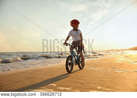 Happy Little Boy Riding Bicycle On Sandy Beach Near Sea At Sunset