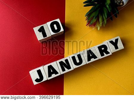 January 10 In Black Letters On Wooden Blocks On A Divided Yellow-red Background .next To A Flower .c