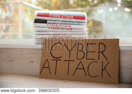 Cardboard With Words Cyber Attack And Newspapers On Window Sill, Closeup
