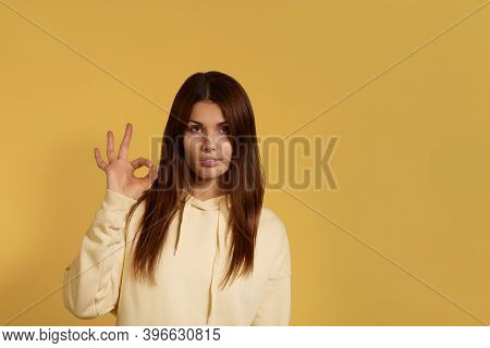 Young Caucasian Woman In A Yellow Hoodie Makes Okay Gesture, Says Ok, Agrees On Something, Confirms