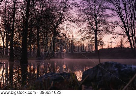 Purple Sunset Over Lake With Stone In Foreground And Tree And Sky Reflection In Dusky Water With Mis