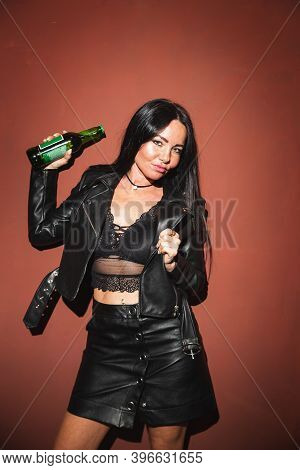 Sexy Brunette Woman In Leather Jacket Leather Skirt And Lace Bralette Posing With Beer Red Wall Back