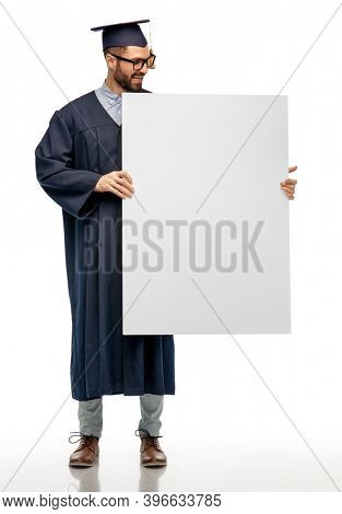 education, graduation and people concept - happy smiling male graduate student in mortar board and bachelor gown holding white board over white background