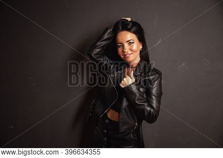 Sexy Unformal Brunette Woman In Leather Jacket Leather Skirt And Lace Bralette Posing Dark Wall Back