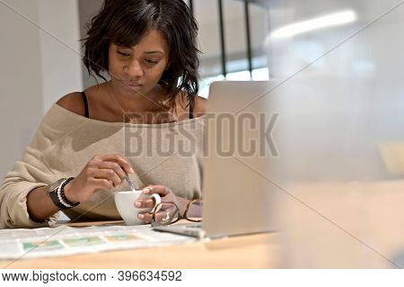 Portrait of middle-aged woman reading the news at home