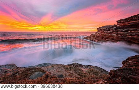 Sunrise Sun Rays Light Up The Sky And Reflect In The Ocean And Rocks In Brilliant Vivid Colours Of O