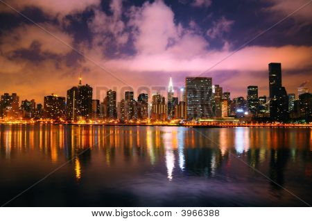 A shot of the New York City skyline at night. poster