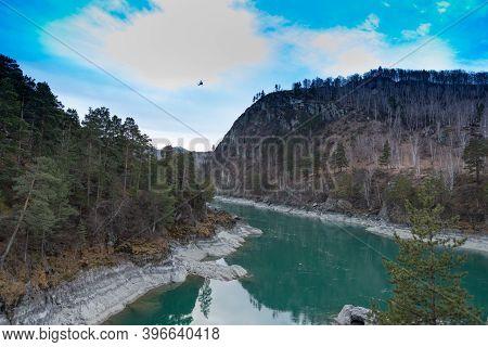 The Katun River In Mountainous Altai, With Rocky Shores, Mountainous Autumn Taiga With Blue Skies An
