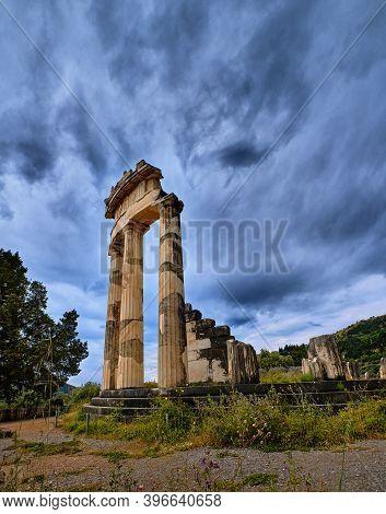 Close Upshot Of Ruins Of Tholos Of Ancient Greek Goddess Athena Pronaia In Delphi, Greece. Three Dor