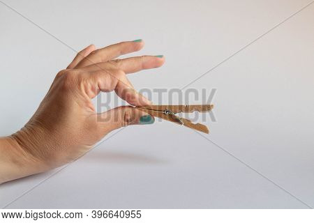 Hand Holding Open Clothespins On White Background