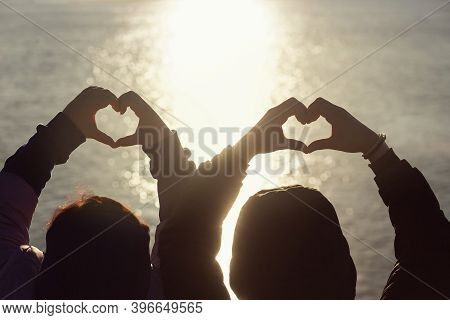 Silhouette Hands Of Man And Woman In Heart Shapes With Sunrise In The Middle And Beach Background. A