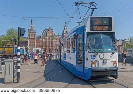 Amsterdam, Netherlands - May 14, 2018: Public Transport Tram And Central Train Station In Amsterdam,