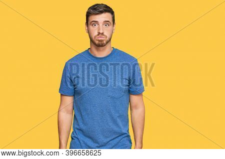 Handsome caucasian man wearing casual clothes puffing cheeks with funny face. mouth inflated with air, crazy expression.