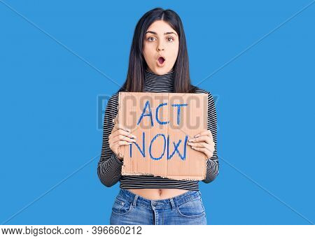 Young beautiful girl holding act now cardboard banner scared and amazed with open mouth for surprise, disbelief face