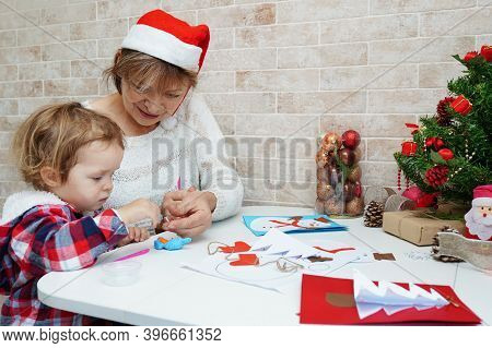Family Making Seasonal Greeting Cards Together At Christmas Time, Grandmother With Granddaughter At