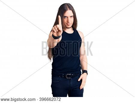 Young adult man with long hair wearing goth style with black clothes pointing with finger up and angry expression, showing no gesture
