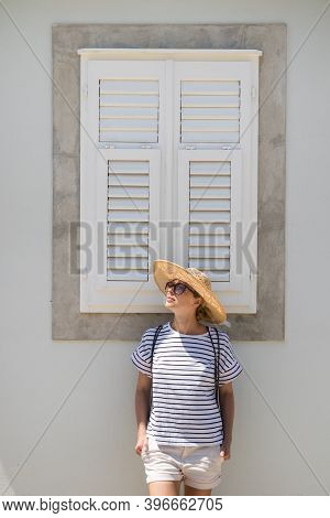 Beautiful Young Female Tourist Woman Wearing Sun Hat, Standing And Relaxing In Front Of Vinatage Woo