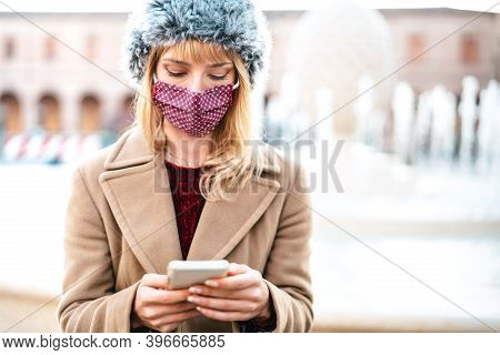 Addicted Woman With Protective Masks Using Tracking App On Mobile Smartphone - Young Worried Milleni