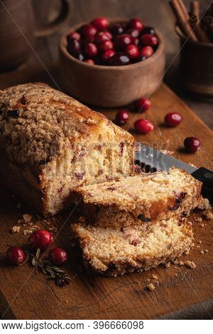 Loaf Of Cranberry Nut Bread Sliced On A Wooden Cutting Board With Bowl Of Cranberries In Background