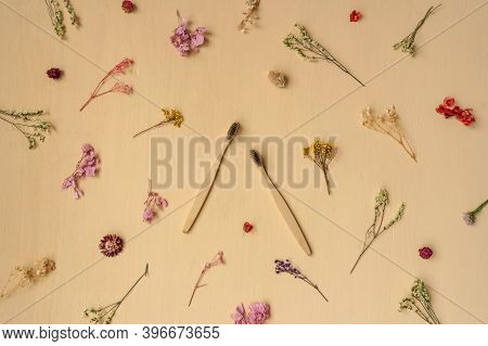 Zero-waste, Biodegradable Bamboo Toothbrush On A Beige Wooden Background With Little Dry Flower Patt